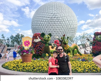 APRIL 27, 2018 - ORLANDO, FLORIDA: FATHER AND SON IN FRONT OF EPCOT DOME AKA SPACESHIP EARTH.