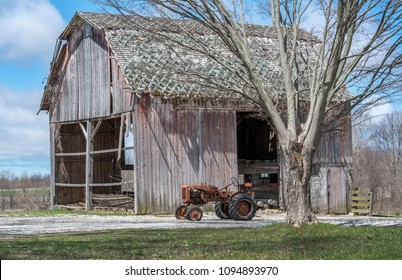 April 28 2018 Buchanan MI USA; an old Allis-Chalers tractor sits outside a rural countryside farm in Michigan