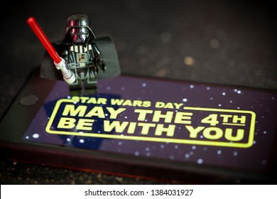 APRIL 28 2019:  Darth Vader Lego Mini Figure with Star Wars wallpaper on an iPhone screen for Star Wars Day concept May the 4th Be With You