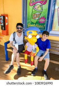 APRIL 29, 2018 - ORLANDO, FLORDIA: FATHER AND SON WITH THE SIMPSONS CHARACTER MILLHOUSE IN BETWEEN THEM AT UNIVERSAL STUDIOS.