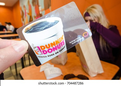 APRIL 3 2016 - CAPE COD, MA: A hand holds up a Dunkin Donuts gift card inside of a Dunkin Donuts franchise store eating area.
