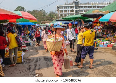April 3 2017 - Kyaing Tong, Myanmar. Shan woman carrying bamboo baskets on yoke in the market