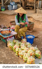 April 3 2017 - Kyaing Tong, Myanmar. Woman in conical hat selling tomatoes in the market