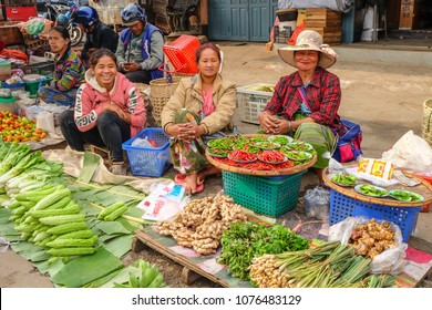 April 3 2017 - Kyaing Tong, Myanmar. Smiling women selling vegetables and herbs in the market