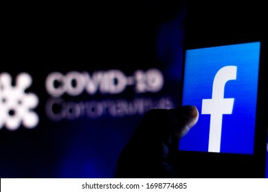 April 5, 2020, Brazil. In this photo illustration the Facebook logo seen displayed on a smartphone with a computer model of the COVID-19 coronavirus in the background.