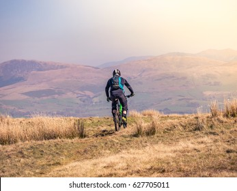 April 8 2017, Cumbria, UK. A mountain biker rides along the crest of Dent Fell in the Lake District, Cumbria, England, with the mountains and fells of the region as a backdrop.