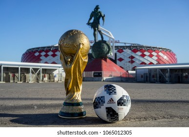 April 9, 2018 Moscow, Russia Trophy of the FIFA World Cup and official ball Adidas Telstar 18 against the backdrop of the Spartak stadium, where the World Cup 2018 matches will be held.
