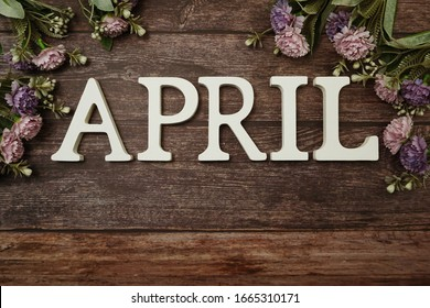 April alphabet letters with flower decoration on wooden background