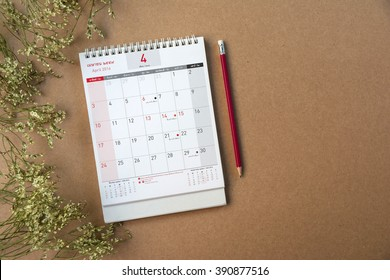 April Calendar 2016(thai Language) and old flower on wood table