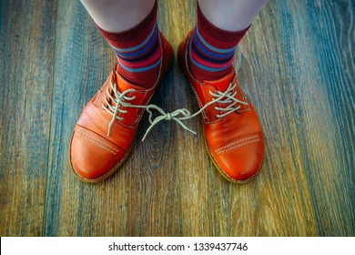 April Fool's Day Shoes. Casual  woman's shoelaces tied together at home in the living room. Red shoes with wooden background