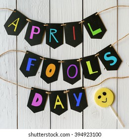 April fools day black banner colorful lettering on white barn wood rustic planks background. Holiday greeting postcard.