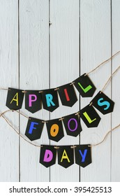 April fools day black banner colorful lettering on white barn wood rustic planks background. Greeting postcard template. Space for text, copy.