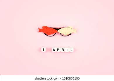 April Fools' Day celebration. Glasses with paper fish and text 1 April on pink background. All Fools' Day, humor, prank, joke concept.