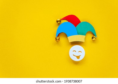 April fools day over yellow background with jester hat. First April card with laughing face. Copy space for text, top view.