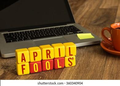 April Fools' written on a wooden cube in a office desk