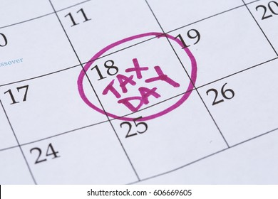 "An April monthly calendar with the 18th circled with the words ""Tax Day"" written in the circle in a bright pink marker."