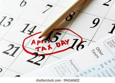 April tax day reminder in a calender  with tax form and pencil, close up