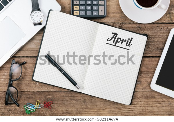 April text in note book on office desk with electronic devices, computer and paper, wood table from above, concept image for blog title or header image.