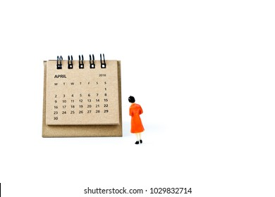 April. Two thousand eighteen year calendar and miniature plastic woman on white background.