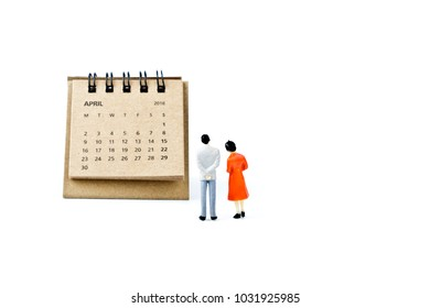 April. Two thousand eighteen year calendar and two miniature plastic figures. Man and woman on white background. Planning for the future marriage, wedding or pregnancy.