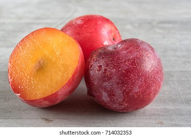 Aprium fruit over a wooden background. Apriums are complex crosses of plums and apricots, requiring several generations of crosses to create a new fruit