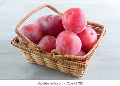 Aprium fruits in a basket over wooden background. Apriums are complex crosses of plums and apricots, requiring several generations of crosses to create a new fruit