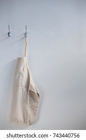 Apron hanging on hook against white wall