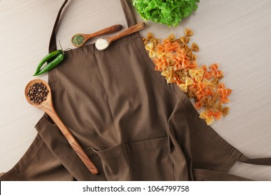 Apron and products for cooking master class on wooden background