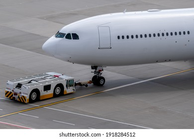 The apron transporter tows a modern narrow-body white passenger aircraft across the airfield of an international airport.