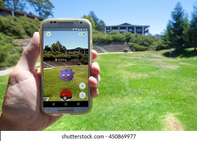 "APTOS, CALIFORNIA - JULY 11, 2016: The hit augmented reality smartphone app ""Pokemon GO"" shows a Pokemon encounter overlain on a college campus in the real world."