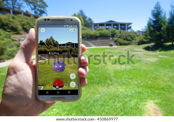 """APTOS, CALIFORNIA - JULY 11, 2016: The hit augmented reality smartphone app """"Pokemon GO"""" shows a Pokemon encounter overlain on a college campus in the real world."""