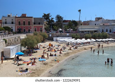 APULIA, ITALY - JUNE 2, 2017: People visit Santa Maria Al Bagno beach in Apulia, Italy. With 50.7 million annual visitors Italy is one of the most visited countries.