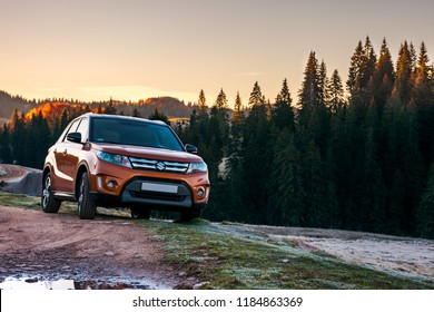 Apuseni, Romania - OCT 15, 2017: orange Suzuki Vitara 4wd suv parked in mountain at sunrise. beautiful autumn scenery with gravel road through spruce forest. travel Europe by car concept