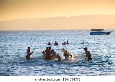 AQABA, JORDAN - AUGUST 19TH, 2016: Young women enjoying a bath in the Red Sea near Aqaba, Jordan, playing with water