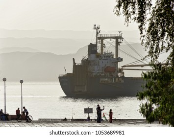 Aqaba, Jordan, March 3, 2018: A large cargo ship passes the Gulf of Aqaba on its way to Eilat and is observed and photographed by a young Jordanian family.