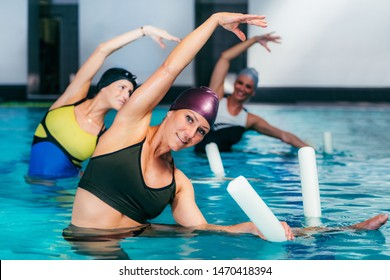 Aqua Aerobic Training with Water Fitness Equipment. Women Training with Swimming Noodles.