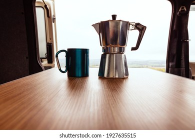 Aqua bialetti coffee maker and camping mug on a wooden table in a T4 camper van