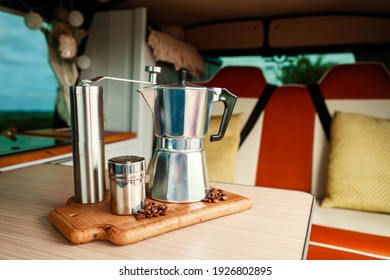 Aqua Bialetti stovetop coffee maker, coffee grinder, chocolate shaker and coffee beans on a wooden tray in a cosy camper van