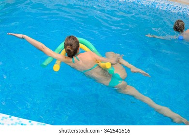Aqua Yoga; a pregnant woman does her yoga exercises at the pool