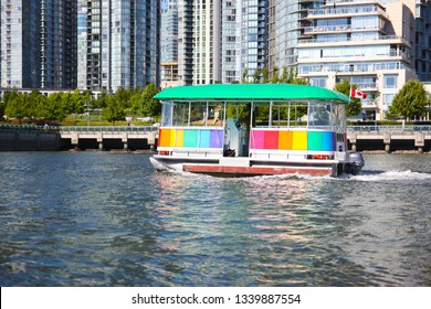 An aquabus or water taxi plying the waters of False Creek toward Granville Island in downtown Vancouver, Canada.
