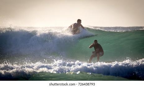 Aquadilla, Puerto Rico, USA - November 24 2014: Sportive people surfing at the coast of Puerto Rico during sunset.