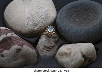 An aquamarine ring among fossils and other rocks.