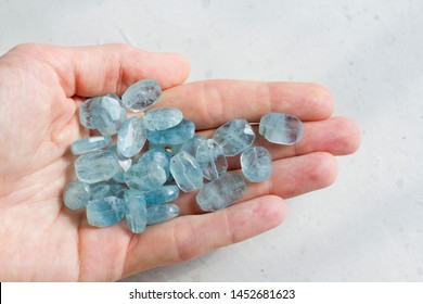 Aquamarine stone lies in the hand. Natural stone Aquamarine on a white background. Female hand. Copy space for your text.