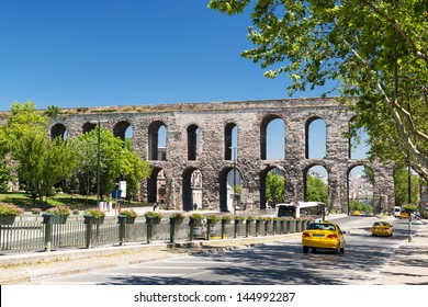 Aqueduct of Valens over city road, Istanbul, Turkey. It is landmark of Istanbul. Cars drive on road in Fatih district in summer. Scenic nice view of Istanbul street. Ancient architecture of Istanbul.