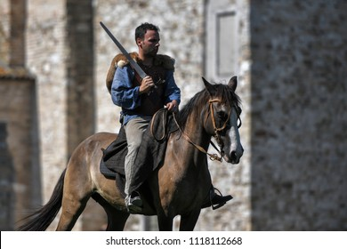 Aquileia, Italy - 17 June 2018: A Celtic Knight in traditional costume holds a sword and rides a horse during Tempora in Aquileia, ancient Roman historical re-enactment