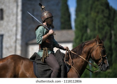 Aquileia, Italy - 17 June 2018: A Celtic Knight in traditional costum holds a sword and rides a horse during Tempora in Aquileia, ancient Roman historical re-enactment