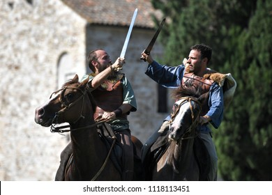 Aquileia, Italy - 17 June 2018: Two Celtic knights in traditional costumes ride horses and battle with the sword during Tempora in Aquileia, ancient Roman historical re-enactment