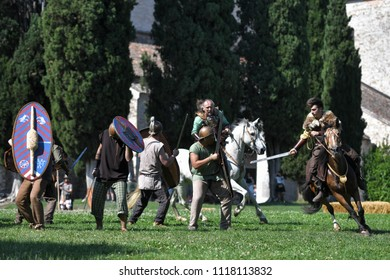 Aquileia, Italy - 17 June 2018:  Celtic knights in traditional costumes ride horses and attack Roman vllagers with swords during Tempora in Aquileia, ancient Roman historical re-enactment