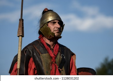 Aquileia, Italy - 17 June 2018: a man dressed as an ancient Roman legionary wears a helmet and holds a spear during Tempora in Aquileia, ancient Roman historical re-enactment