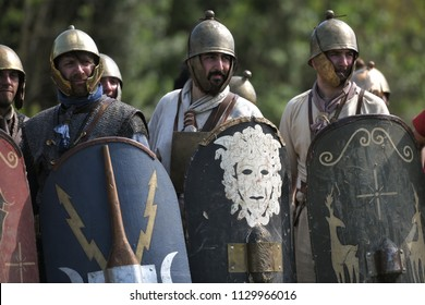 Aquileia, Italy - 17 June 2018: Roman legionaries wearing helmets and shields look on in defence formation during Tempora in Aquileia, an ancient Roman historical re-enactment